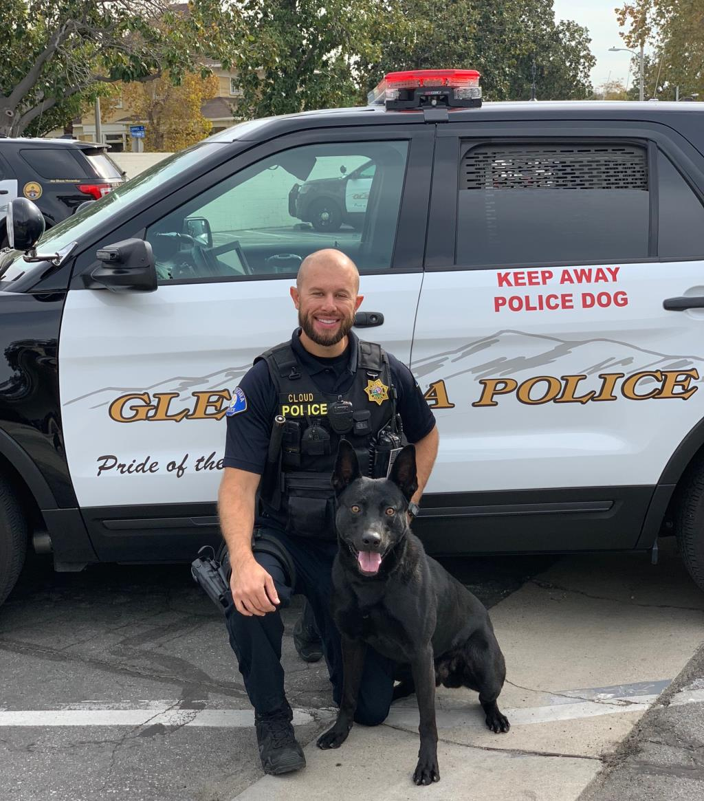 Officer Cloud poses in front of a police car with his K9 partner Sam.
