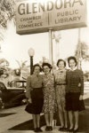 Women pose in front of 1930 Glendora Library sign